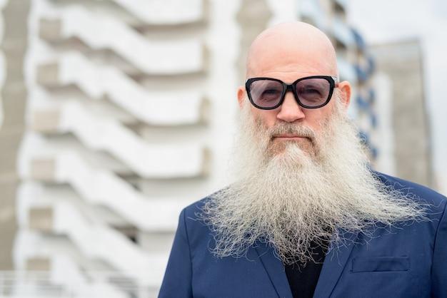 Gesicht des reifen kahlen bärtigen geschäftsmannes im anzug, der draußen sonnenbrille trägt