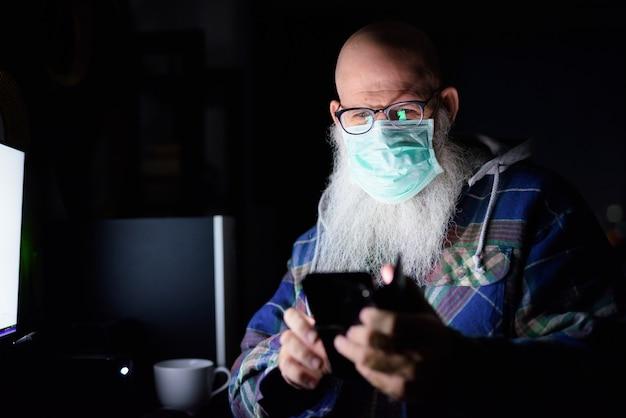 Gesicht des reifen kahlen bärtigen mannes mit maske unter verwendung des telefons, während spät in der nacht von zu hause aus arbeitend