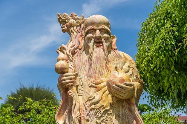 Gesicht einer alten chinesischen kriegerstatue oder eines gottchinesen in einem buddhistischen tempel in der stadt danang, vietnam, nah oben