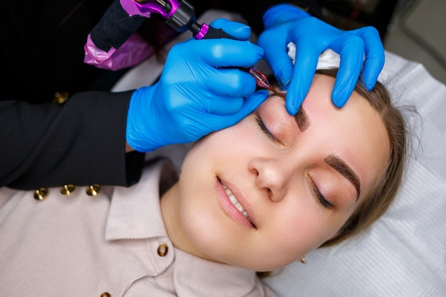 Gesicht einer schönen frau mit buschigen augenbrauen in einem schönheitssalon. permanent make-up für die augenbrauen. kosmetikerin macht augenbrauentattoo für frauen. schönheitsverfahren.