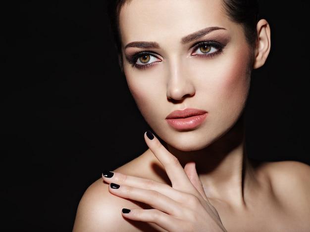 Gesicht eines schönen mädchens mit mode-make-up und schwarzen nägeln, die im studio über dunklem hintergrund aufwerfen
