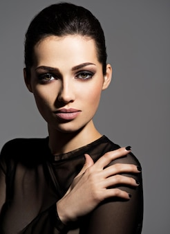 Gesicht eines schönen mädchens mit mode-make-up und schwarzen nägeln, die über dunkler wand aufwerfen