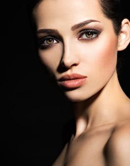 Gesicht eines schönen mädchens mit rauchigen augen make-up, das im studio über dunklem hintergrund aufwirft
