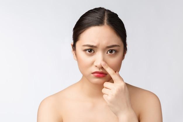 Gesicht hautproblem - junge frau unglücklich berühren ihre haut isoliert, konzept für die hautpflege, asiatisch