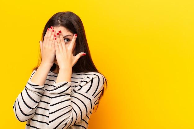 Gesicht mit den händen bedecken, mit überraschtem ausdruck zwischen den fingern spähen und zur seite schauen