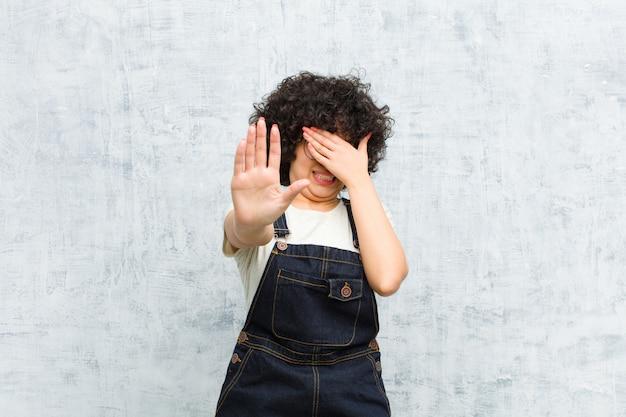 Gesicht mit der hand bedecken und andere hand nach vorne legen, um anzuhalten, fotos oder bilder ablehnen