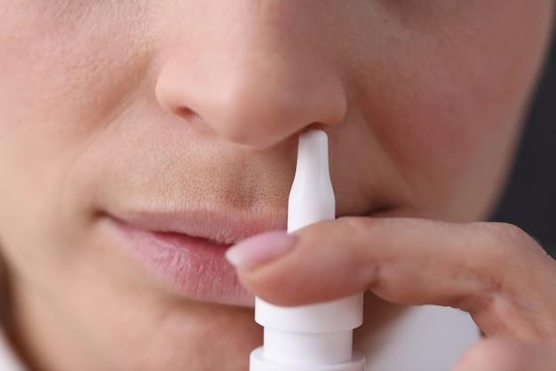 Gesicht mit weißer nasensprayflasche. nasopharyngealkrankheit und allergiekonzept