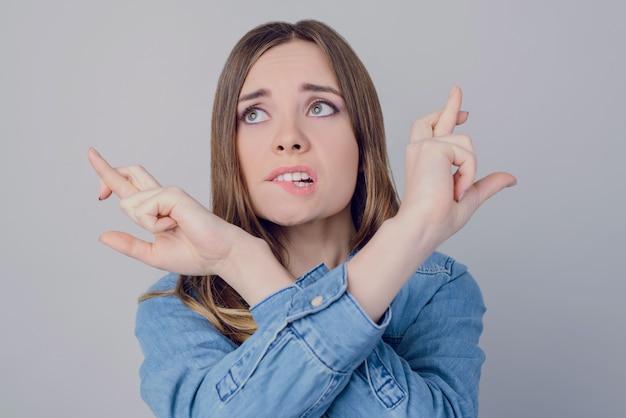 Gesicht nervös deprimiert geschäft bitten geschäftsfrau casual zwei prüfungen vertrauen lustige freude spaß grimassieren bildung karrierekonzept. nahaufnahme porträt eines süßen mädchens, das einen wunsch auf grauem hintergrund macht