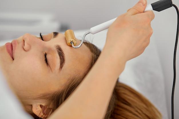 Gesichts-madero-massage mit einem gesichtsroller, junge frau im schönheitssalon nahaufnahme erhalten verfahren von professionellen medizinischen arbeitern comsetologen