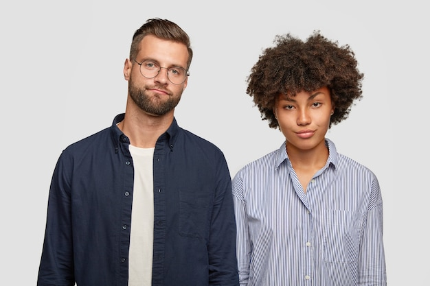 Gesichtsausdrücke und emotionskonzept. die horizontale ansicht einer verwirrten frau und eines mannes gemischter rassen hat ernsthafte blicke missfallen