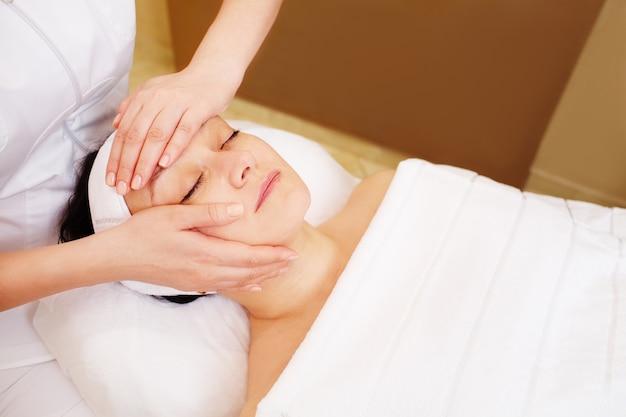 Gesichtsbehandlung mit professioneller massage der kosmetikerin