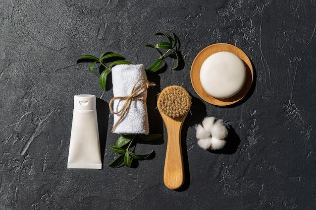 Gesichtscreme, massagebürste und seifenstück mit weißem handtuch und baumwollblume auf schwarzem hintergrund. bio-kosmetik. behandlung spa schönheit hautpflege, gesundheitswesen. markenwerbung. produktfoto.