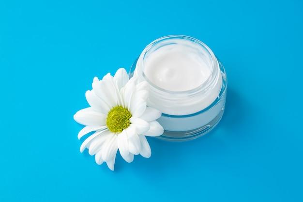 Gesichtscremeglas mit weißer kamillenblume auf blauem hintergrund. kräuterlotion in glasflasche, naturkosmetik.