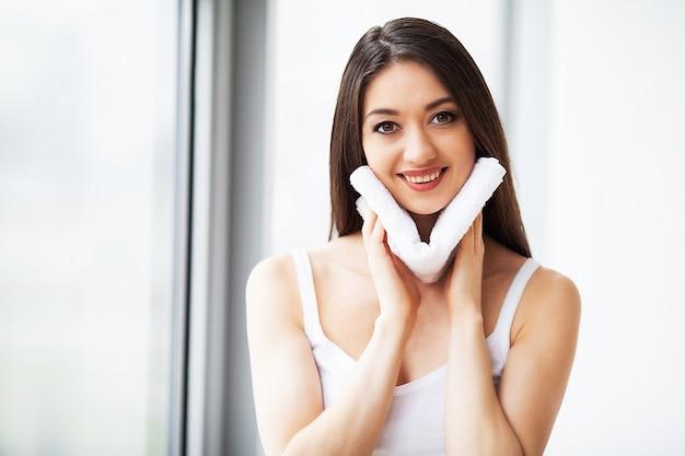 Gesichtshaut reinigen. schönes glückliches mädchen-waschendes gesicht