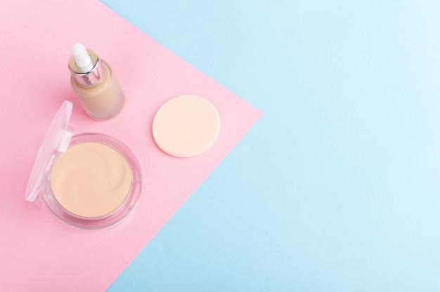 Gesichtshautkorrekturkosmetik auf hellpurpurnen, rosa und blauen pastellhintergrund.