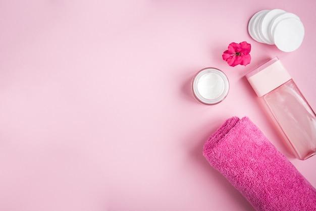 Gesichtshygiene. handtuch, tonic, creme, wattepad und blume auf rosa hintergrund.
