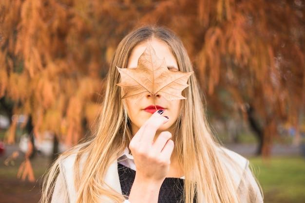 Gesichtslose blonde frau, die blatt nach gesicht hält