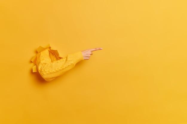 Gesichtslose frau bricht arm durch papier gelbe wand zeigt rechts an der leerstelle gibt ratschläge zum kauf eines abonnements schlägt vor, auf den link zu klicken zeigt richtung.