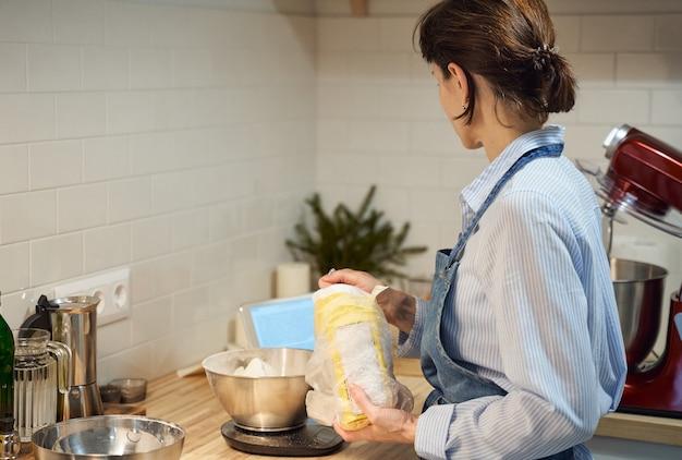 Gesichtslose frau, die teig auf küchentisch zu hause kocht und backt