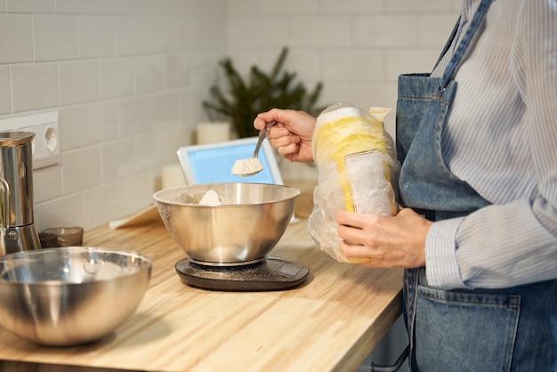 Gesichtslose frau, die teig auf küchentisch zu hause, wohnung, mehl, waage, schalen, digitales tablett mit rezepten auf tisch kocht und backt. hausgemachtes essen