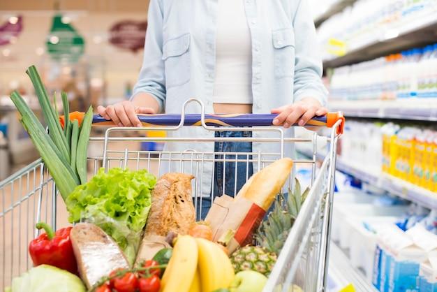 Gesichtslose frau, die warenkorb am supermarkt fährt