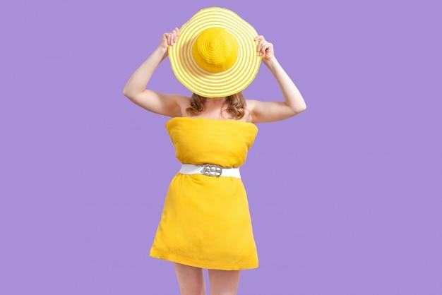 Gesichtslose frau im gelben kissenkleid bedeckte ihr gesicht mit hut auf lila hintergrund. sommerkonzept. pillow challenge wegen isolation zu hause bleiben.