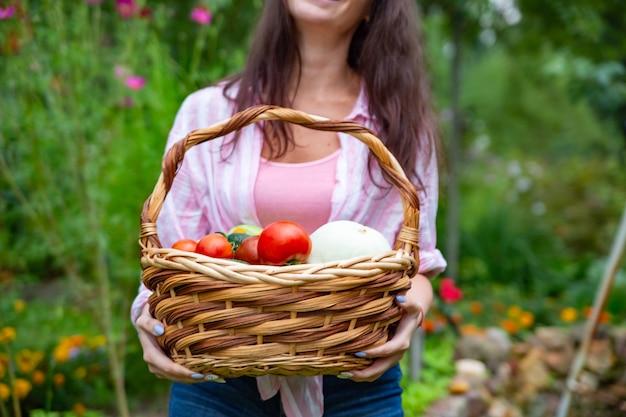 Gesichtslose, glücklich lächelnde bäuerin hält einen korb mit gemüse aus ihrem garten