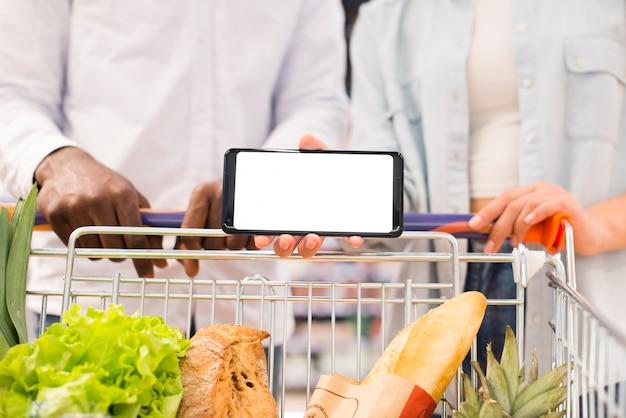 Gesichtslose paare mit dem warenkorb, der smartphone am supermarkt hält