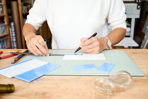 Gesichtslose unternehmerin, die glas im handwerkerarbeitsraum schneidet