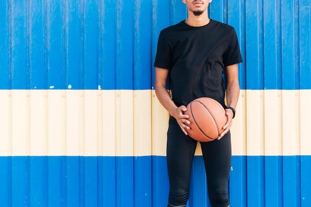 Gesichtsloser athletischer mann, der gegen die wand hält basketball steht