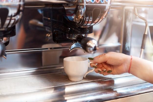 Gesichtsloser barista, der leckeren kaffee über eine kaffeemaschine macht