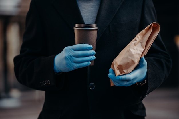 Gesichtsloser geschäftsmann hält essen zum mitnehmen und eine tasse kaffee zum mitnehmen, trägt aus sicherheitsgründen medizinische gummihandschuhe
