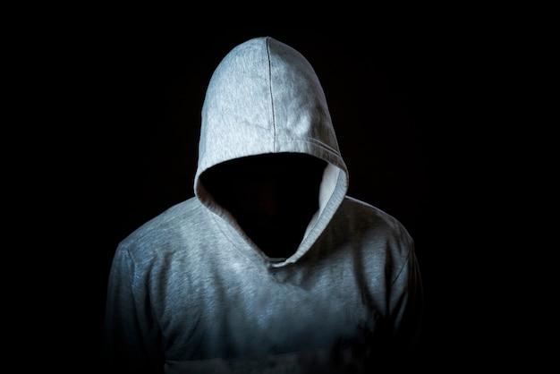 Gesichtsloser inkognito-mann trägt kapuze auf dunklem hintergrund isoliert b