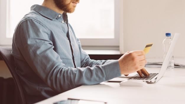 Gesichtsloser junger mann mit kreditkarte in der hand beim online-shopping auf laptop
