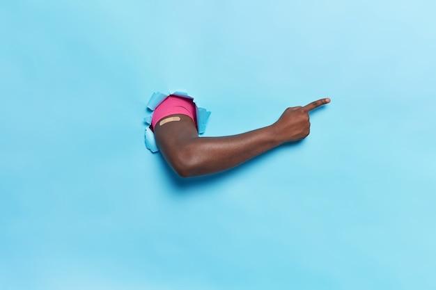 Gesichtsloser mann bricht arm, trägt gips, nachdem er geimpft wurde, erhält eine impfung, die auf einen leeren raum auf blauem hintergrund hinweist