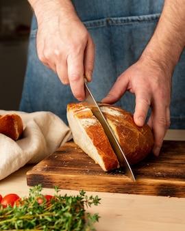 Gesichtsloser mann, der frisches selbstgebackenes knuspriges brot mit großem messer auf holzbrett auf küchentisch schneidet. hausgemachte bäckerei, vertikal