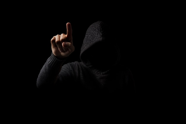 Gesichtsloser mann in einer kapuze mit einem finger taucht in einer dunkelheit auf