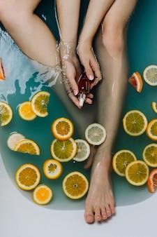Gesichtsloser schuss der frau in einem badezimmer, das mit blauem wasser und verschiedenen geschnittenen zitrusfrüchten gefüllt ist, die serum in ihren händen halten