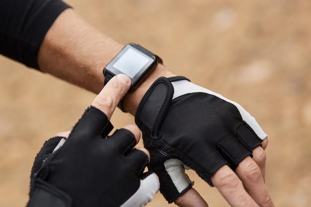 Gesichtsloses bild der mannhand, die intelligente uhr und sportliche handschuhe trägt