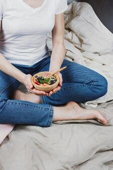 Gesichtsloses porträt der frau in den jeans und im weißen hemd in ihrem bett, das vegane smoothie-schüssel hält