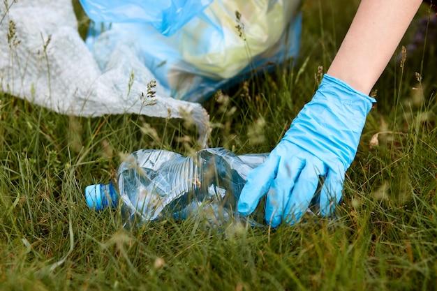 Gesichtsloses porträt von personenhänden, die plastikflasche vom boden aufheben, wiese säubern und sie in müllsack, müll auf gras, frauenhand in blauem handschuh legen.
