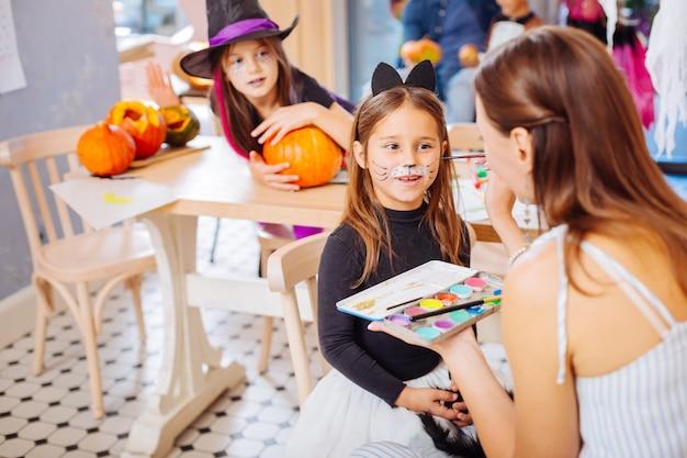Gesichtsmalerei. professionelle gesichtsbemalung, die sich glücklich fühlt, während sie mit dem kleinen mädchen arbeitet, das katze halloween kostüm trägt
