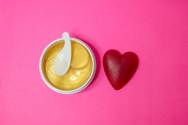 Gesichtsmaske, behälter mit anhebenden flecken des goldenen anti-aging-kollagens unter augen für frauengesichtspflege, auf rosa hintergrund. exklusives kosmetisches produkt für hautpflege und behandlung.
