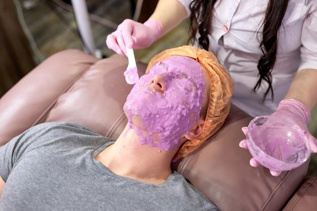 Gesichtsmaske des mannes im spa-salon, männlich erhalten schönheitsverfahren. massage im gesicht. abgeschnittene kosmetikerin mit schüssel, die flüssigkeit auf haut aufträgt, gesichtsbehandlung gegen akne