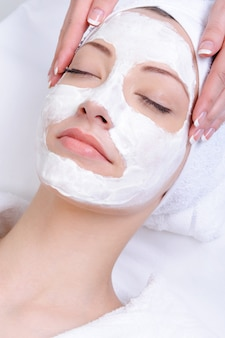 Gesichtsmaske für junge frau im salon der schönheitsnahaufnahme