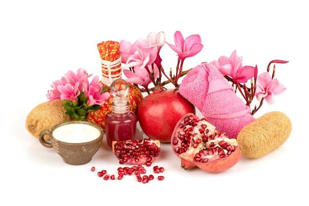 Gesichtsmaske mit granatapfelfrüchten und joghurt lokalisiert auf weißem hintergrund.