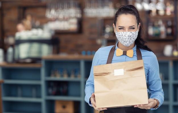 Gesichtsmaske tragender restaurantmitarbeiter übergibt während der sperrung das paket zum mitnehmen.