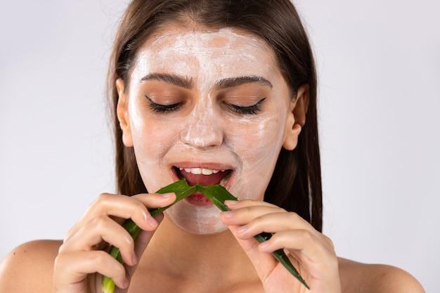 Gesichtsmaske und langes gesundes haar. in den händen eines zerbrochenen blattes aloe vera. hochwertiges foto