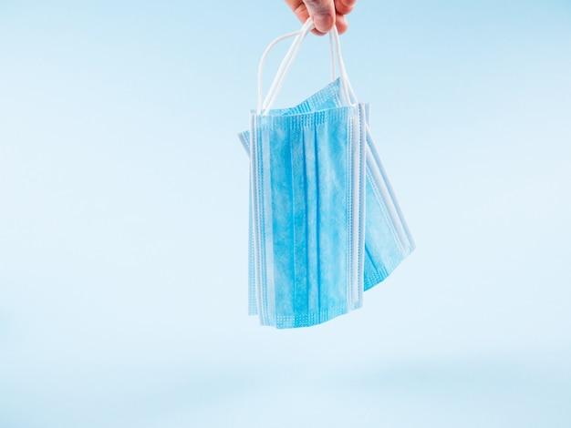 Gesichtsmasken auf blau als symbol der covid19-pandemie