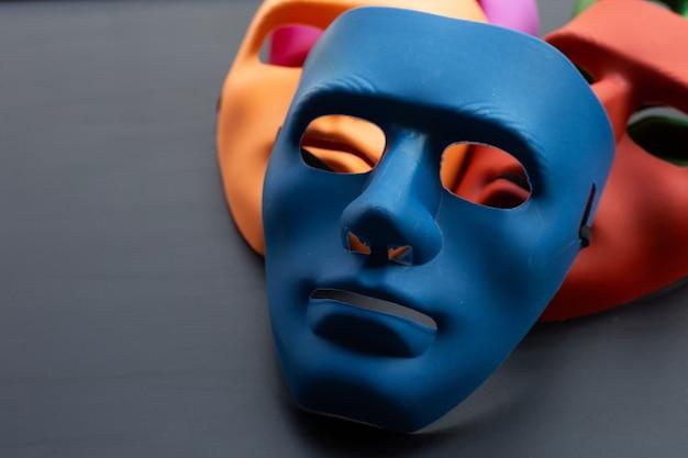 Gesichtsmasken auf dunkler oberfläche. speicherplatz kopieren